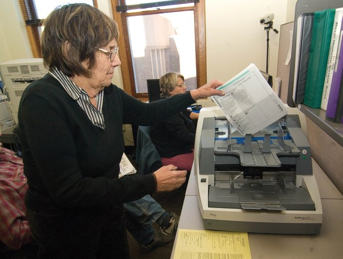 Election judge Jane Romberg pulls a ballot out of the scanner after it was counted Monday afternoon at the Routt County Elections Office inside the Routt County Courthouse in Steamboat Springs.