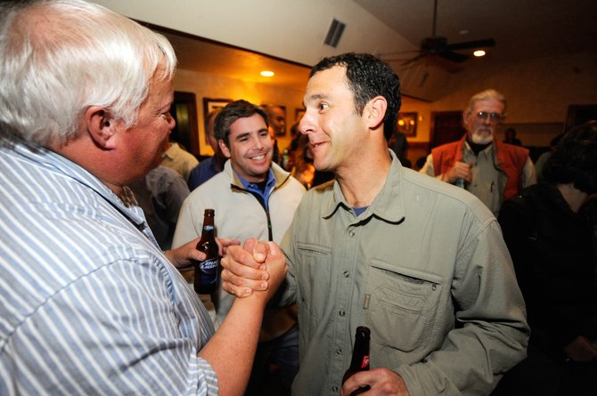 Kenny Reisman, right, is congratulated by supporter Roger Good on Tuesday night at the Old Town Pub after learning the news that Reisman beat Ken Solomon in the Steamboat Springs City Council District 2 race.
