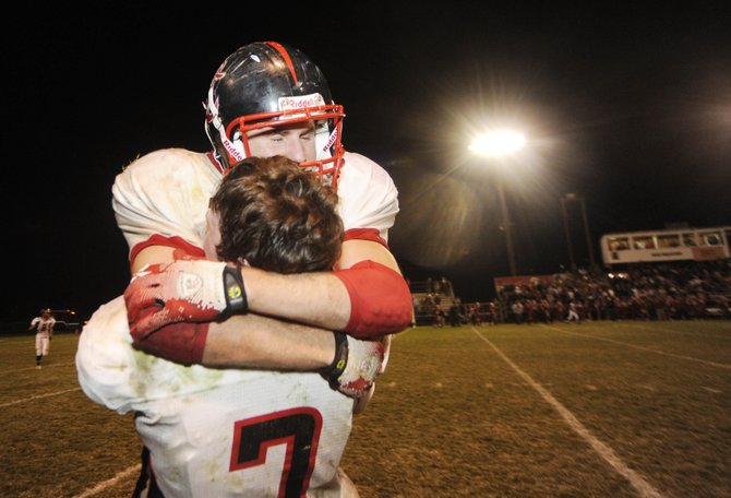 Steamboat Springs High School senior Joe Dover jumps and hugs quarterback Austin Hinder after Steamboat's 30-21 win over Glenwood Springs High School on Friday in Glenwood. By beating Glenwood, Steamboat earned the Western Slope League title.