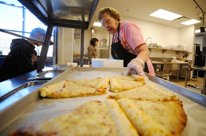 Soda Creek Elementary School cafeteria worker Loraine Boyle serves pizza during lunch Friday.