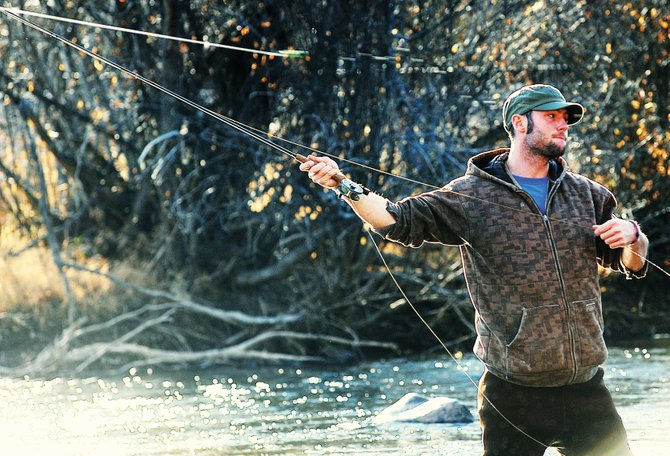 Torre Saterstrom whips his fly rod Thursday afternoon while fishing in the Yampa River in downtown Steamboat Springs. While summer has come and gone, there is no shortage of fishing opportunities available for outdoorsmen in Routt County.