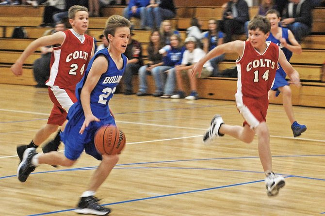 Taft Cleverly drives down the court during the eighth-grade Craig Middle School basketball game Tuesday night against Rawlins Middle School. Cleverly led the team in scoring with 24 points in the Bulldogs' 40-27 win against the Colts.