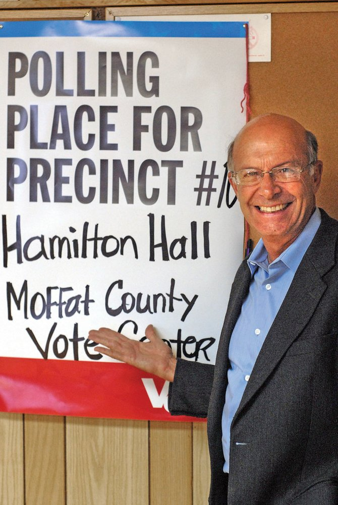 Bernie Buescher, Colorado secretary of state, poses in front of a sign for Colorado's newest voting precinct Tuesday morning at Hamilton Hall. Buescher presented grant money to remodel the center to meet state requirements and reopen the hall as a voting center.