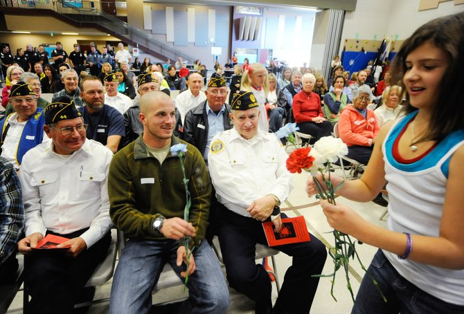 Soda Creek Elementary School fifth-grader Ellie Kavanaugh hands flowers to veterans Jim Stanko, left, Gar Williams, right, and active-duty U.S. Army soldier Mike Buchan during a Veterans Day ceremony Wednesday at Soda Creek. Buchan has been on leave and returns to Afghanistan today.