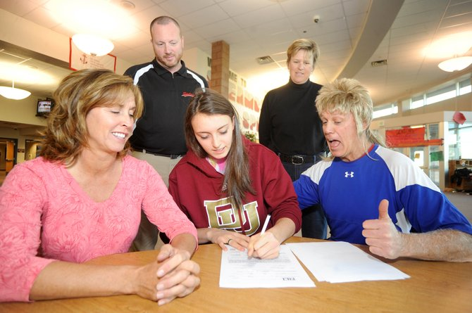 Buddy King gives the thumbs up as his daughter Colleen signs a letter of intent to play volleyball at the University of Denver on Wednesday at Steamboat Springs High School. Colleen also was joined by her mother Joanie, left, principal Kevin Taulman and coach Wendy Hall.