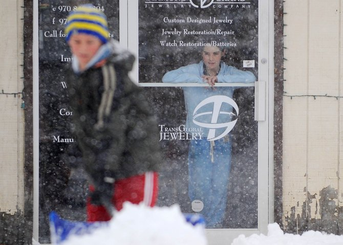 Hayleigh Aurin, 11, watches her friend Matthew Thielemann shovel snow Friday from in front of Diamond Brand Jewelry.