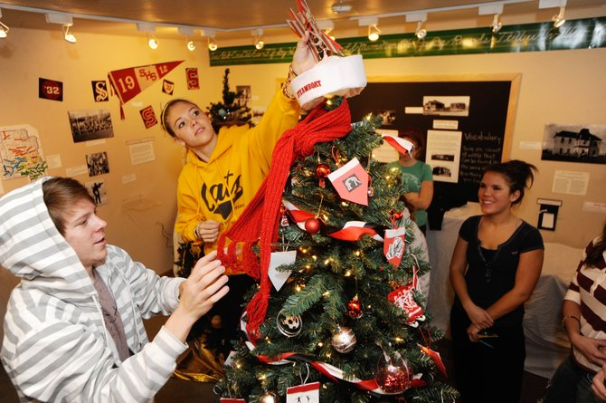 Steamboat Springs High School National Honor Society members David Mucklow, from left, and Jaime Winter put the final touches on a Christmas tree for this year's Festival of Trees, a fundraiser that benefits the Tread of Pioneers Museum.