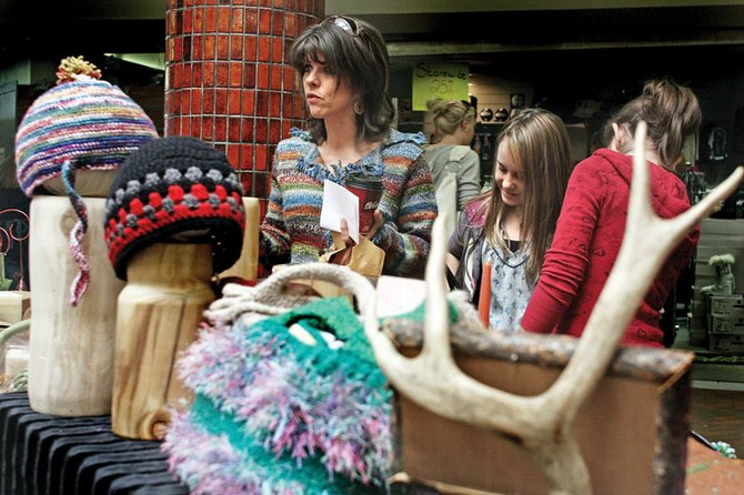 Karleen Kennedy, left, looks over a booth with Kaytlin Herring, 10, center, and Katie Kennedy, 12, during the holiday craft show Saturday at the Centennial Mall. Many Craig residents sifted through local wares to find holiday gifts for friends and family. Centennial Mall will host another event on Dec. 11 and 12.