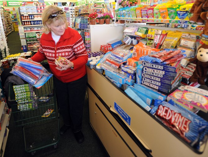 Lynne McNasby loads up the check-out conveyor belt Sunday at the Dollar Tree in Central Park Plaza. The goods will be sent to troops overseas for the holidays.