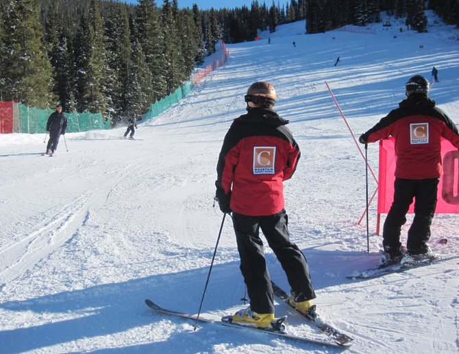 A pair of Copper Mountain staff members keep an eye on early season skiers Tuesday afternoon.