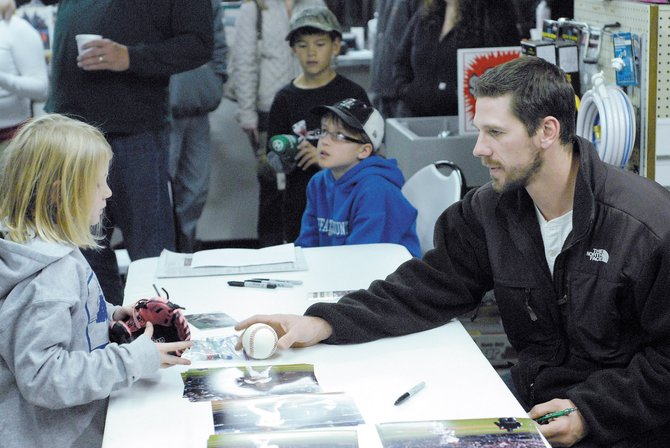 Philadelphia Phillies pitcher Cliff Lee signs autographs for fans Wednesday night at Auto Parts of Craig and Airtek Filters. The 2008 American League Cy Young Award winner is in Northwest Colorado on a hunting trip.