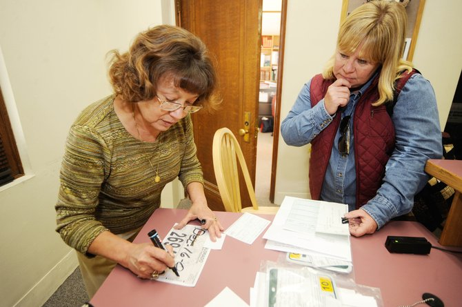 Routt County Motor Vehicle Deputy Clerk Mae King assists Hayden resident Joy Booco on Wednesday at the Routt County Courthouse. County Finance Director Dan Strnad is projecting a $400,000 boost to county funds next year from increased vehicle fees.