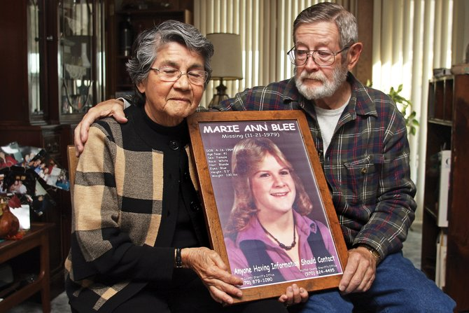 "Paul and Mona Blee hold a framed poster of their daughter, Marie, who was last seen on Nov. 21, 1979, and reported missing on Nov. 22, when she was 15. The photo used for the poster was a school picture from Hayden High School, and is the last known picture taken of Marie. Before this photo of Paul and Mona was taken, Paul said, ""It will be like the family portrait we never had."""