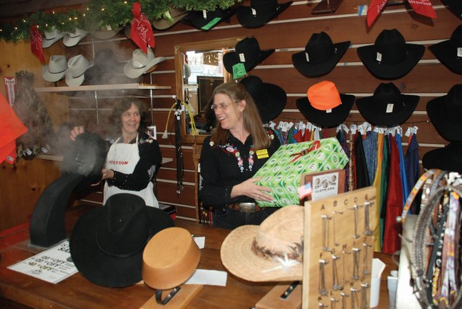 KImberly Stenerson, left, and Andra Hansen steam and shape customers' cowboy hats and wrap gift boxes at F.M. Light and Sons on Friday. Although some say it signals the start of the holiday shopping season, Steamboat retailers don't see the influx of bargain shoppers on Black Friday that metro areas often experience.