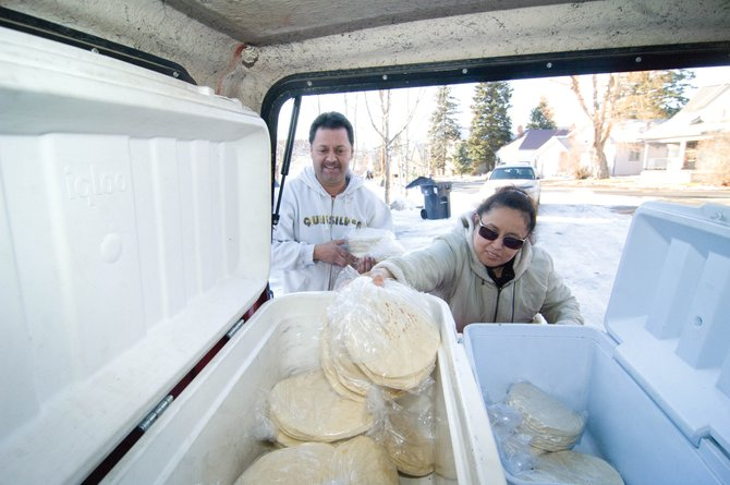 Luz Mendoza, right, and Arturo Velazquez pull tortillas out of coolers they keep in the back of their pickup before knocking on doors in downtown Steamboat Springs on Thursday afternoon.