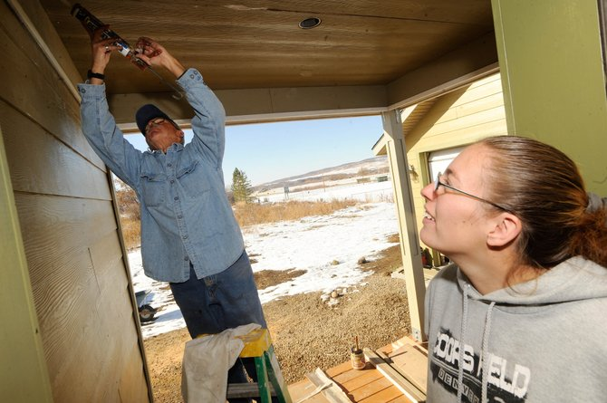 Future Routt County Habitat for Humanity homeowner Amanda Archuleta watches volunteer Jim Southard do some caulking work on the Hayden home. Southard has been volunteering at the house once a week.