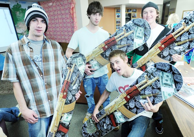 Colorado Mountain College students Tom Moroney, from left, Josh Pacheco, Andrew Steezy-Parker and Elliot Martinez pose with the snowboards they were tasked with selling Thursday night in Willett Hall on the CMC campus. The sale was part of the ski and snowboard business and retail sales class.