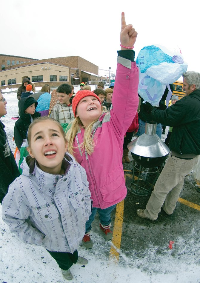 Bailey Zabel, left, and Maritza Weidel watch as their tissue-paper balloon climbs high into the air above Steamboat Springs Middle School on Monday morning. The students launched tissue-paper balloons as part of a science project to teach them about how hot air rises.