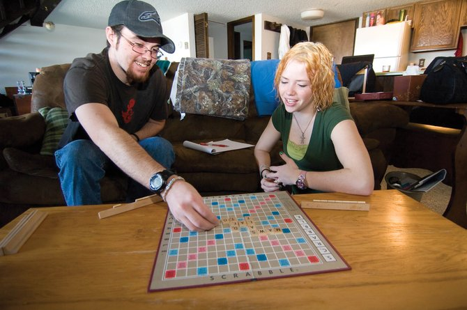 Clayton Huyser and his fiancee, Darcy Wisecup, play a game of Scrabble inside the couple's Fish Creek Falls condominium. Huyser has returned home after suffering a stroke nearly a year ago.
