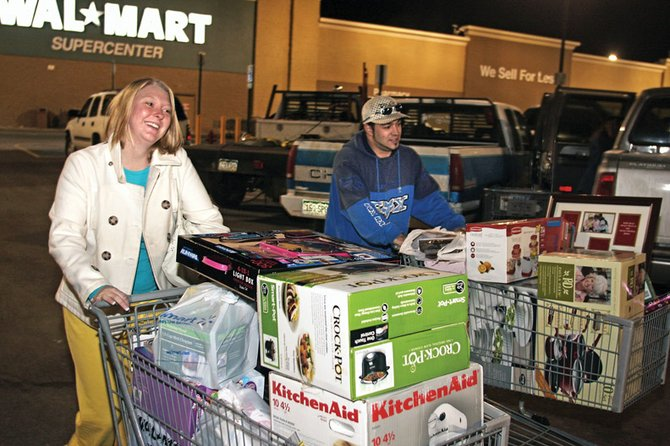 Jess McQuay, left, and Chris Pierce push their overflowing carts through the Wal-Mart parking lot after the Black Friday sale. The two said they had been at the store since 3 a.m., picking out items and waiting for the 5 a.m. sale to start.