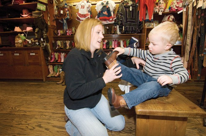 Jennifer Jacobsen helps her son Jones with a boot while shopping at F.M. Light &amp; Sons on Friday afternoon. The downtown business was filled with people looking for bargains and holiday gifts the day after Thanksgiving.