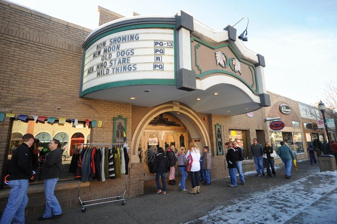 A crowd waits for the Chief Plaza Theater to open its doors Friday afternoon.  The building, which also is home to Summit Shades and Blossom, is being put on the market.