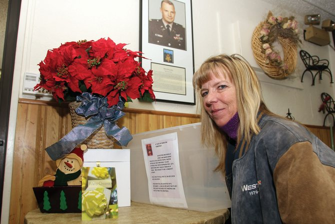 Cory Phillips sits in the Veterans of Foreign Wars Post 4265 restaurant, along with one of her several collection bins that are placed at businesses across Craig. Phillips hopes to collect enough jerky and baked goods to send care packages to local troops stationed overseas for the holiday season.