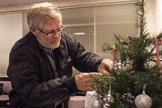 Gary Meyer places a bulb decoration on a Christmas tree during a Celebration of Life ceremony Tuesday at the Northwest Colorado Visiting Nurse Association. People wrote the names of missed loved ones on the bulbs in their memory.