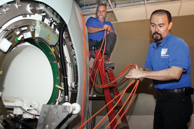 Dale Quick, right, takes fiber optic cables from Kim Ford while installing the new MRI machine Wednesday at The Memorial Hospital. The two are medical equipment technicians who travel across the country making installations for Remetronix, a Florida-based company.