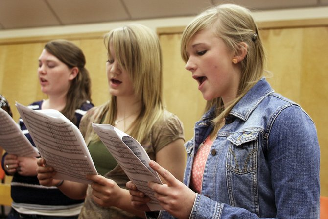 Moffat County High School Jazz Choir members Kat Thompson, from right, Kyra McClellan and Austin Lee rehearse for tonight's concert with the Steamboat Springs Orchestra. The concert will start at 7 p.m. in the MCHS auditorium.