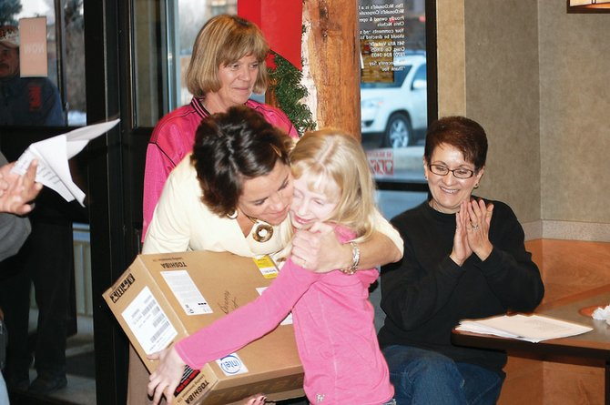 Ridgeview Elementary School student Brianna Burkett gets a hug from her principal, Julie Baker, as she receives a new laptop computer Thursday at McDonald's. She won the computer for selling 331 tickets to the Substance Abuse Prevention Program's 2009 pancake breakfast.