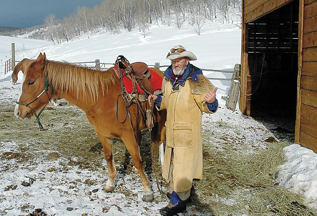 Ray Heid, of Del's Triangle 3 Ranch, uns­addles after a winter trail ride in 2006. The ranch decided not to increase its prices this winter.