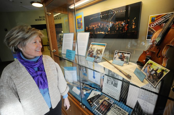 Flute player Mary Beth Norris stands by a display at the Bud Werner Memorial Library about the history of the Steamboat Springs Orchestra, which she helped found. The orchestra plays at 8 p.m. today and 3 p.m. Sunday at the Steamboat Christian Center.