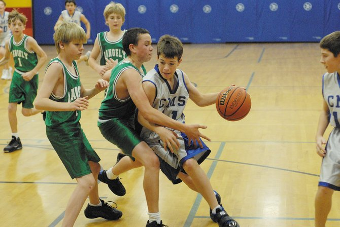 Craig Middle School's Joe Camilletti, center, drives through an onslaught of Rangely Middle School defenders on his way to two points. The seventh-grade team defeated Rangely, 30-5, in its first game Saturday. Both the seventh- and eighth-grade Bulldogs beat Meeker to claim the middle school championship.