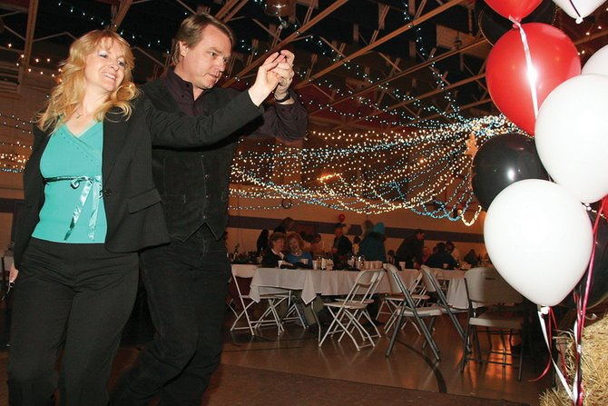 Janet Wright, left, and her husband, Wayne, do a cowboy cha-cha on the dance floor during the Cowboy Christmas fundraiser Saturday night at the Boys & Girls Club of Craig. The event is the main fundraiser for the club.