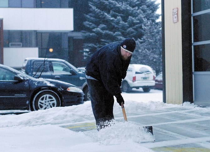 Garrick Hafen shovels snow Monday afternoon around the garage doors of Lube Plus on Victory Way. A spokesperson from the National Weather Service said the Craig area can expect about 8 inches of snow this week.