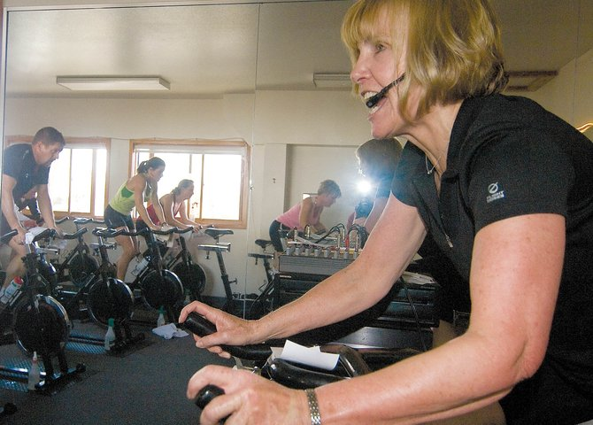 Fitness Director Simonne Oliver motivates her students to dig deeper during a spinning class 