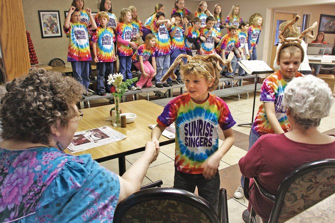 Jeremy Looper, center, and Camron Ludgate, right, shake hands with the residents at Sandrock Ridge Care & Rehab during a performance Tuesday afternoon by the Sunrise Singers. The Sunrise Singers are a group of fourth- and fifth-graders from Sunset Elementary School.