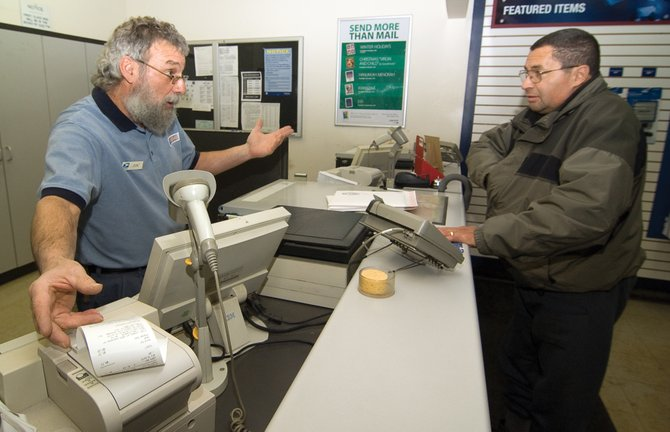 Post office employee Don Ciavarra helps customer Michael Condie at the Sundance Plaza branch of the U.S. Postal Service.  The post office reports that retail postal service there will end Jan. 15, and post office box service there could end March 15.