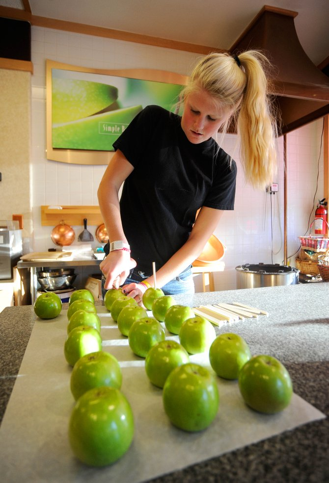 Rocky Mountain Chocolate Factory employee Kiki Adams prepares apples for caramel at the downtown Steamboat Springs store Thursday afternoon.
