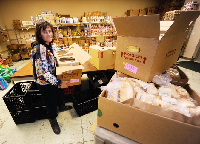 LIFT-UP of Routt County volunteer Candace Noriega loads a cart with bread for the food bank Friday.