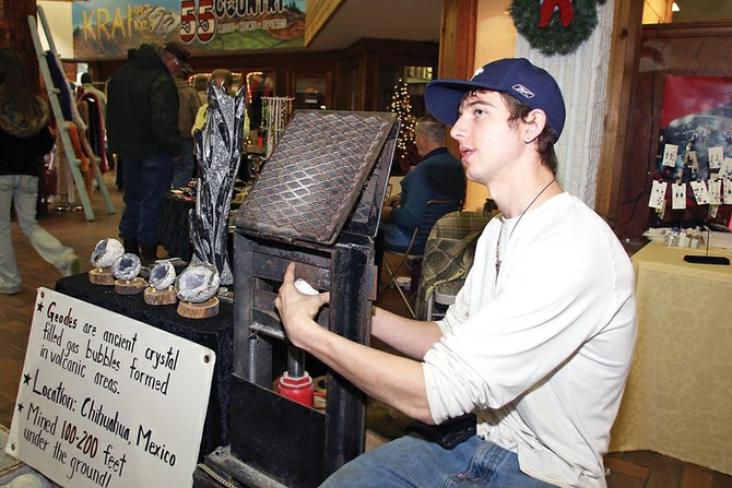 Dusty Atkinson places a geode into the geodetine, a tool used to split the rocks, during Saturday's Winter Arts and Crafts Show at Centennial Mall. Atkinson works with his father's company, Stone Works, based out of Steamboat Springs.