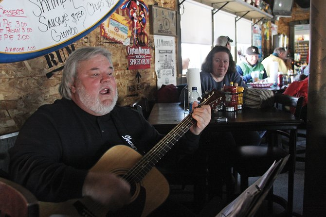 Anthony Tremaine plays his guitar Friday at J.W. Snacks during Lights Out Lunch, a statewide event to raise energy conservation awareness. Organizations participating in the blackout turned off their lights, radios and televisions to conserve energy.