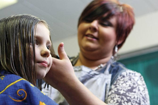 Courtney Lytle, 6, has her hair styled by Crystal Walker at All About You Salon. Courtney's haircut was free because she donated her hair to Locks Of Love, an organization that makes wigs for children with cancer.