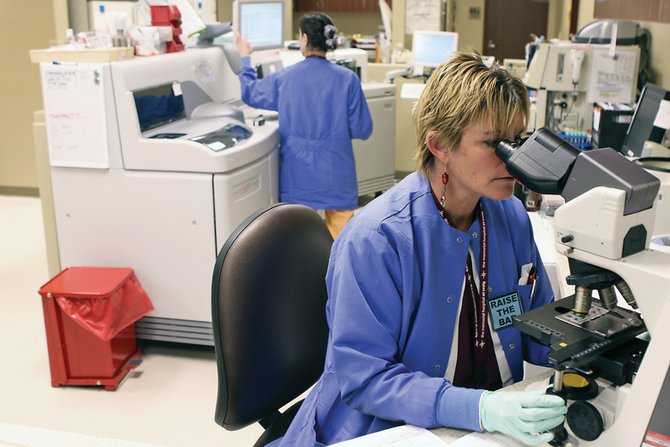 Chris Gardner, a medical technician at The Memorial Hospital's laboratory, uses her HMX hematology analyzer to test blood samples Wednesday afternoon at TMH. The hospital is looking at implementing a program that would allow people to get certain tests without a doctor's referral.