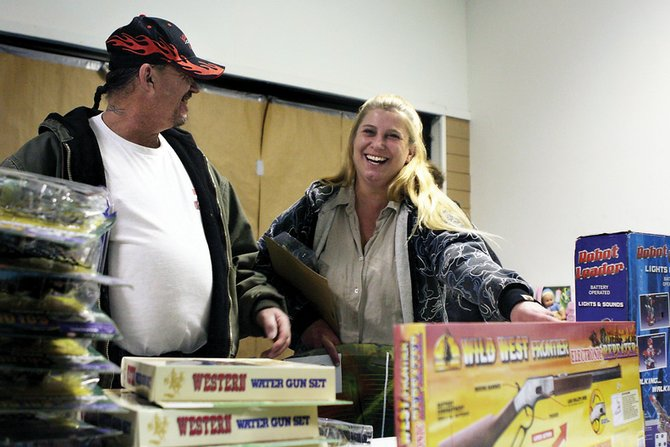 Vinnie Turner, left, and Sandra Bernhardt smile as they pick out a few extra gifts to put under the tree during the Christmas for Kids toy pickup. Organizers said the drive helped nearly 300 families make this season a little merrier for their children.