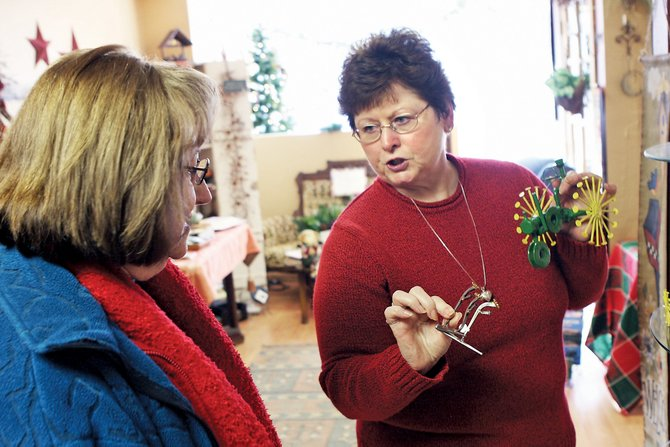 Liz Davis, owner of The Giving Tree, shows some of her merchandise to holiday shopper Pat Pearce on Thursday at her store. Pearce said she comes to The Giving Tree every year to shop for Christmas presents because everything in the store is so unique.