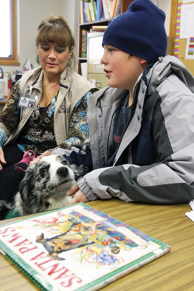"Trystan Campbell pets Jenny, a Delta Society certified therapy dog owned by Amy Andrews. Trystan read part of the book ""Santa Paws"" to Jenny at Ridgeview Elementary School. The program is designed to help kids feel comfortable reading out loud without the anxiety in the classroom."