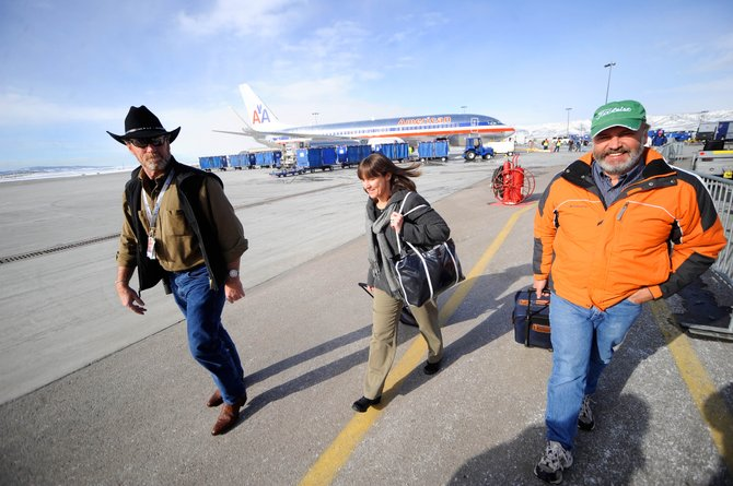 Yampa Valley Regional Airport Assistant Airport Manager Dean Smith, left, visits with Tim and Susan Dunlop, of DeKalb, Ill., as they walk to the terminal Thursday after getting off an American Airlines flight that arrived on time from Chicago. The jet launched the arrival of ski season air service at the airport.