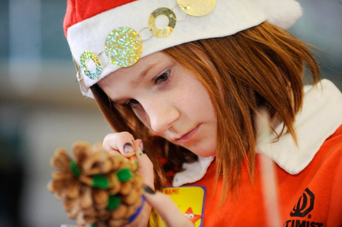 "MaKayla Woods paints a pine cone Saturday during ""Santa's Workshop,"" presented by the Optimist Club of Steamboat Springs at the Boys & Girls Club of Steamboat Springs. The free event included opportunities for children and their families to give to five local and national organizations."